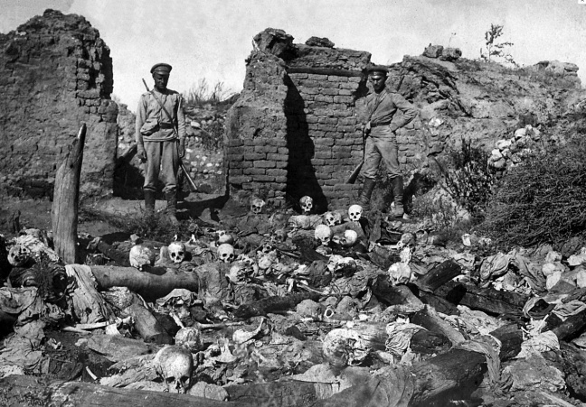Soldiers standing over skulls of victims from the Armenian village of Sheyxalan in 1915, believed to be victims of the Armenian Holocaust